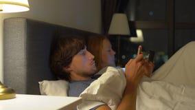 在与智能手机和片剂个人计算机的床其中每一张上的男人和妇女 在婚姻和男女两性之间的关系的问题 股票视频
