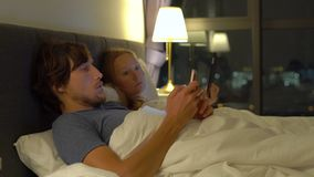 在与智能手机和片剂个人计算机的床其中每一张上的男人和妇女 在婚姻和男女两性之间的关系的问题 股票录像