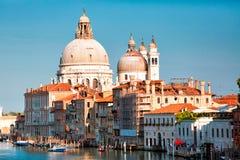 在与有趣的云彩的日落,威尼斯,意大利期间,大运河和大教堂圣玛丽亚della的出色的意见向致敬 免版税图库摄影