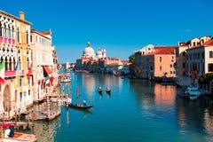 在与有趣的云彩的日落,威尼斯,意大利期间,大运河和大教堂圣玛丽亚della的出色的意见向致敬 免版税库存照片