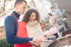 在与朋友的一顿野餐期间人和女孩烹调烤肉食物 免版税库存照片