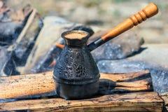在与木把柄的一金属cezve被烹调的无奶咖啡在早晨关闭的一个营火风景看法 库存图片