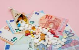 在与欧洲钞票的欧元包裹的片剂在桃红色背景 医疗概念 图库摄影