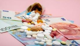 在与欧洲钞票的欧元包裹的片剂在桃红色背景 医疗概念 免版税库存图片