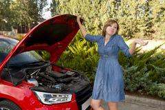 在与残破的发动机失败或崩溃事故的路旁搁浅的绝望和迷茫的妇女 免版税库存图片