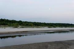 在与沙子和云彩的日落以后靠岸 库存图片