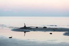 在与沙子和云彩的日落以后靠岸 免版税库存照片