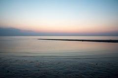在与沙子和云彩的日落以后靠岸 免版税库存图片