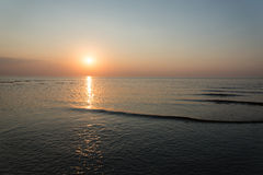 在与沙子和云彩的日落以后靠岸 图库摄影