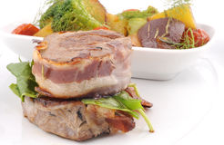 在与沙拉配菜的烟肉包裹的猪排 库存照片