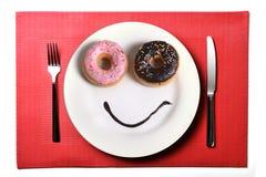 在与油炸圈饼眼睛和巧克力糖浆的盘做的兴高采烈的愉快的面孔作为微笑在糖和甜瘾营养方面 免版税库存照片