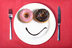 在与油炸圈饼眼睛和巧克力糖浆的盘做的兴高采烈的愉快的面孔作为微笑在糖和甜瘾营养方面 免版税库存图片