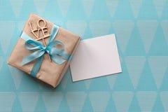 在与浅兰的丝带的包装纸包裹的礼物盒在与贺卡的蓝色背景 o 自由空间 免版税库存照片