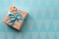 在与浅兰的丝带的包装纸包裹的礼物盒在蓝色背景 自由空间 免版税库存图片
