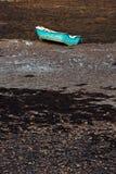 在与浪潮的海底搁浅的一艘蓝色划艇为 免版税库存图片