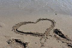 在与海和波浪的海滩沙子画的心脏 库存照片