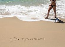 在与海运海浪的沙子写的加勒比 库存照片