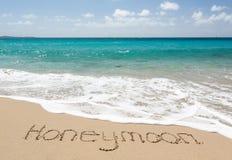 在与海运海浪的沙子写的蜜月 免版税库存图片