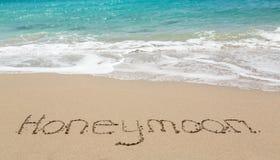 在与海运海浪的沙子写的蜜月 库存照片
