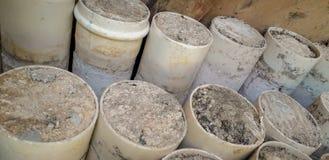 在与混凝土的地板上堆积的白色PVC管子 免版税库存照片