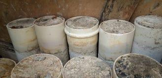在与混凝土的地板上堆积的白色PVC管子 库存照片