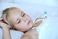 在与温度计的床上的病的小女孩 库存图片
