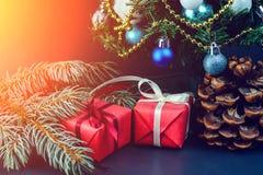 在与白色丝带und的一张红色纸和礼物包裹的杉木锥体 库存照片