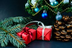 在与白色丝带und的一张红色纸和礼物包裹的杉木锥体 库存图片