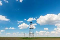 在与白色云彩的蓝天描出的老油和煤气船具,在春天 免版税图库摄影