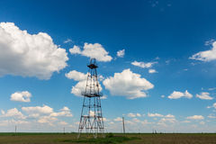 在与白色云彩的蓝天描出的老油和煤气船具,在春天 图库摄影