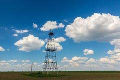 在与白色云彩的蓝天描出的老油和煤气船具,在春天 免版税库存图片