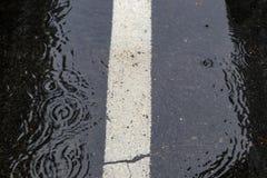 在与白色停车处条纹的一个黑沥青停车场合并的起波纹的水背景在雨期间 库存照片