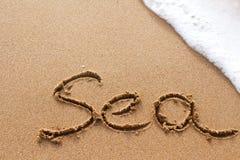 在与白色波浪的沙子写的海在背景 库存图片