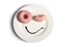 在与眨眼睛眼睛和巧克力糖浆的油炸圈饼的盘做的兴高采烈的愉快的面孔作为在糖和甜瘾的微笑 免版税库存图片