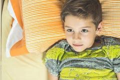 在与眼睛的床上的孩子打开 免版税库存图片