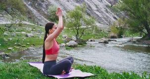 在与石头的令人惊讶的风景和在席子的河少女实践的瑜伽中间她有凝思 股票录像