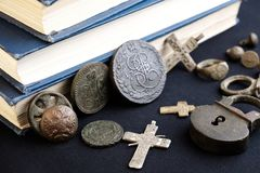 在与破旧的捆绑的旧书旁边是19世纪的古老俄国硬币,收藏家的宗教标志 库存图片