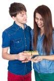 在与礼物的白色背景在手中隔绝的愉快的年轻美好的夫妇 库存图片