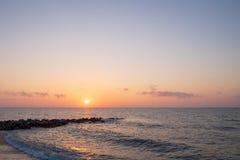 在与突出入海的岩石的海滩在日出时 免版税库存照片