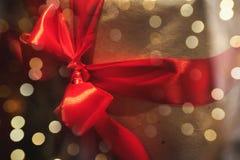 在与红色丝带的工艺纸包裹的礼物盒在背景o 免版税库存照片