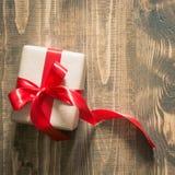 在与红色丝带的工艺纸包裹的礼物盒木表面上 库存图片