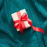 在与红色丝带的工艺纸包裹的礼物盒被编织的表面上 顶视图 库存图片