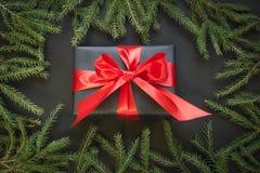 在与红色丝带的黑纸包裹的礼物盒在黑表面上的女性手上 顶视图 袋子看板卡圣诞节霜klaus ・圣诞老人天空 库存图片