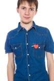 在与红色纸心脏的白色背景隔绝的有吸引力的男孩身分在他的口袋 库存照片
