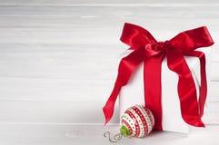 在与红色缎丝带的有装饰品的白皮书和箱子包裹的圣诞节礼物在灰色白板背景,文本室 免版税库存图片