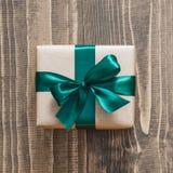 在与绿色丝带的工艺纸包裹的礼物盒木表面上 顶视图 图库摄影