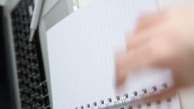 在与绿色植物的工作表上迅速移动灰色罐的,女性手打开笔记本 影视素材