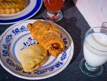 在与芝麻籽的新月形面包涂黄油烘烤与米尔新鲜的玻璃  库存照片