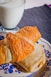 在与芝麻籽的新月形面包涂黄油烘烤与米尔新鲜的玻璃  免版税库存照片