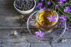 在与花的木背景驱散的开花的萨莉,收集的和干酿造清凉茶有用每杯子  免版税库存照片